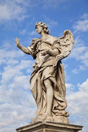 angeli: Angel with the Nail on Ponte SantAngelo, Rome, Italy, Angel created by renaissance artist, Bernini, against blue sky. Stock Photo