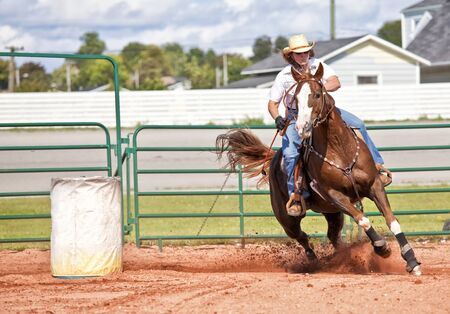 Western horse and rider competing in pole bending and barrel racing competition. Stock Photo