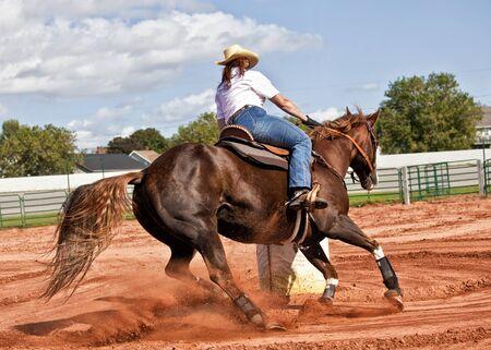 rodeo americano: Caballo y jinete occidental compitiendo en carreras de competici�n polo de flexi�n y el barril.