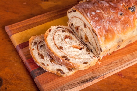 raisins: Homemade rolled cinnamon raisin bread on a wooden cutting board. Stock Photo