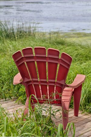 adirondack chair: Red plastic Adirondack chairs placed for a view of the river.