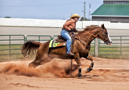 rodeo cowboy: Western horse and rider competing in pole bending and barrel racing competition. Stock Photo