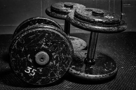 but: An old but well used set of dumbbells at the gym in black and white  Stock Photo