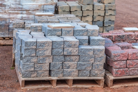 cement pile: Stacks of various colored concrete pavers (paving stone) or patio blocks organized on wooden pallets and for sale in a retail setting such as a garden center or building supply.
