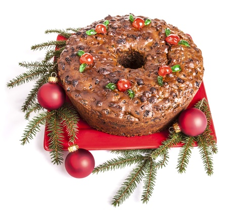 fruitcake: Traditional homemade Christmas fruitcake decorated with candied cherries, boughs and baubles