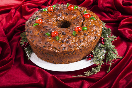 Traditional homemade Christmas fruitcake decorated with candied cherries, boughs and baubles Stock Photo - 22551568