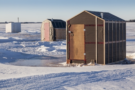 ice fishing: Rustic ice fishing shacks out on the ice.