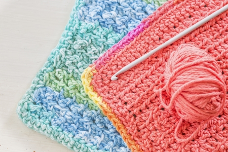 crochet: Two hand crotched dishcloths with a crotchet hook and ball of yarn.