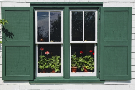 gables: Pots of flowering geraniums in the window of Green Gables House, made famous by the Anne of Green Gables books by L. M. Montgomery.  Located in Cavendish, Prince Edward Island, Canada.