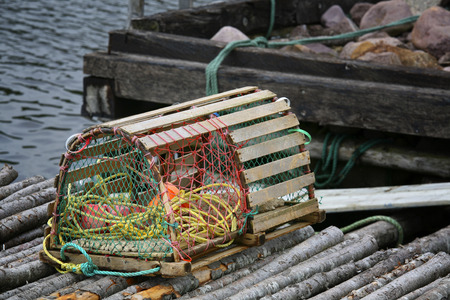lobster pots: A wooden lobster trap with buoys and rope on a Newfoundland, Canada wharf.