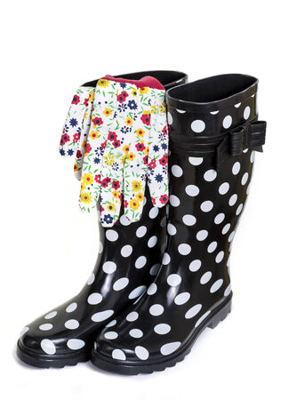 A colorful gardening outfit with polka dot rubber boots and floral patterned gardening gloves  Focus is on the gloves  photo