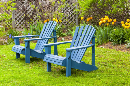 adirondack chair: A pair of wooden Adirondack chairs in the spring garden.