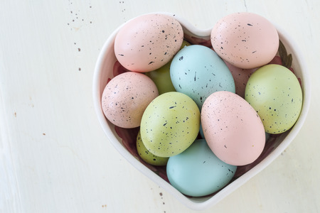 speckled wood: Speckled Easter eggs in a variety of colors. Arranged in a heart shaped bowl. Stock Photo