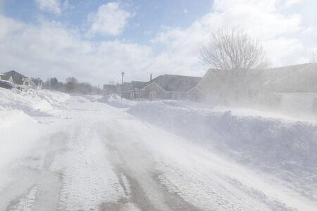 zichtbaarheid: Slecht zicht met een sterke wind waait sneeuw rond tijdens een sneeuwstorm in suburbia. Stockfoto