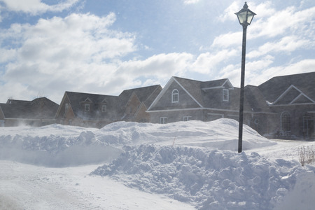 Poor visibility with strong winds blowing snow around during a snow storm in suburbia. Stock Photo