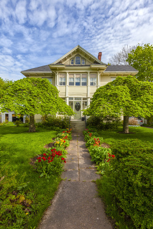 Beautiful heritage home with flowering tulips in a spring garden.