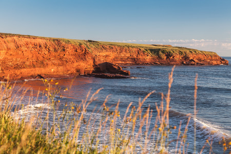 The rocky shore of Prince Edward Island at daybreak illuminating the cliffs and rocks bright red. photo