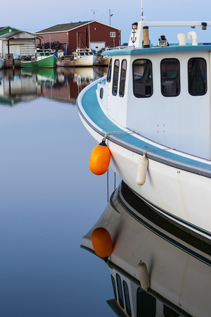 lobster boat: Evening light on lobster boats tied up at the wharf in rural Prince Edward Island, Canada