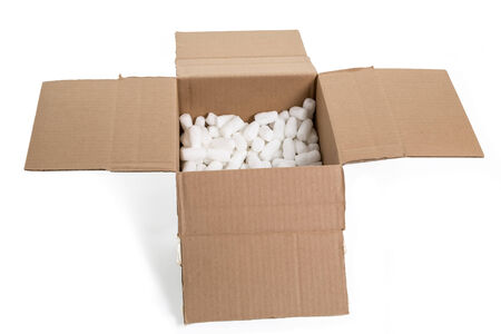 Open corrugated cardboard box that has been cut down and partially filled with styrofoam peanuts. photo