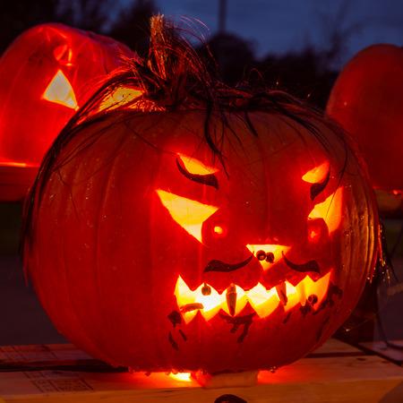 hand carved: Menacing hand carved Halloween pumpkin glowing in the dark.