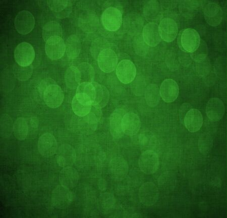 vignettes: Abstract textured green or Christmas  background with bright circular shapes and a darker vignette border