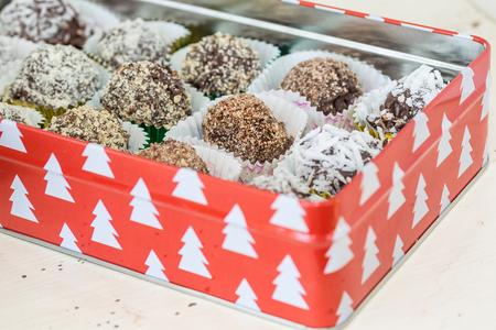 revestimientos: Trufas de chocolate hechas en casa con diferentes recubrimientos como el coco, almendras trituradas o avellanas o nueces. Cada coloca en una taza decorativa y colocados en una caja de Navidad.