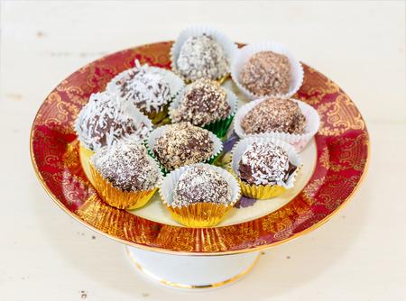 revestimientos: Trufas de chocolate hechas en casa con diferentes recubrimientos como el coco, almendras trituradas o avellanas o nueces. Cada uno en una taza de l�mina decorativa y se coloca en un plato de porcelana de pedestal. Foto de archivo