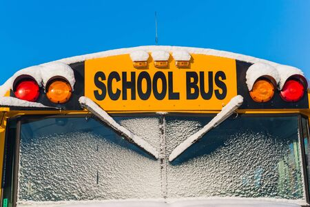 The front of a school bus after a fresh winter snowfall. Stock Photo