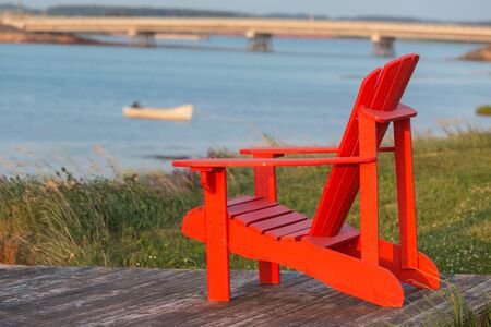 lawn chair: A red lawn chair with a view of a seaside vista in rural Prince Edward Island, Canada.