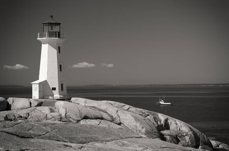 Sepia Peggys Cove lighthouse, Nova Scotia, Canada. Lobster boat gathering traps in the background.