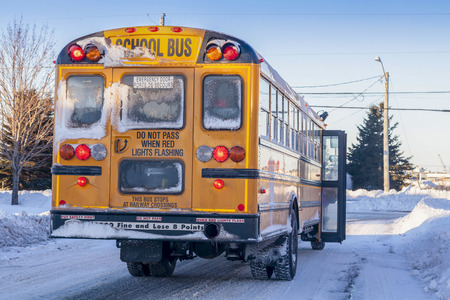 snowbank: A typical yellow school bus stopped to pick up passengers on an extremelyy cold winter day.