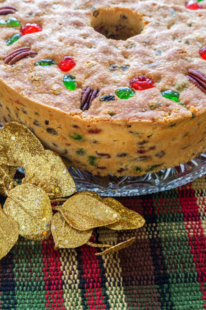 Traditional light fruitcake decorated with pecans and cherries.