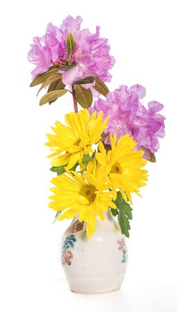 A spring bouquet of yellow mums and lavender PJM rhodoendrons in a ceramic vase. Stock Photo