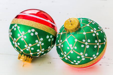 Red and green glass Christmas ornaments on a white distressed wooden background.