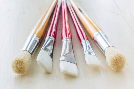 A variety of paint brushes on a wooden table. Stock Photo