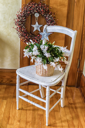 A Christmas cactus sits on an old chair with various folk art Christmas decorations.