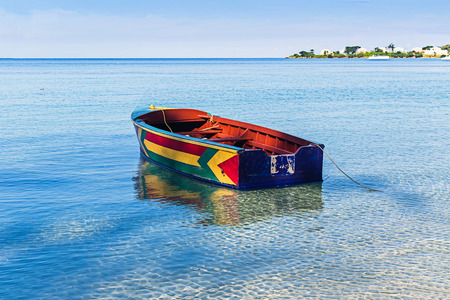 A colorful Jamaican boat floating along the shores of Bloody Bay, Negril.