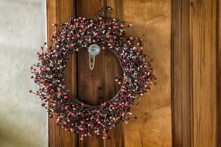 A Christmas wreath hangs on an old door. With vintage effects.