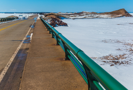 Highway running through Prince Edward Island National Park along the frozen shoreline and dunes.