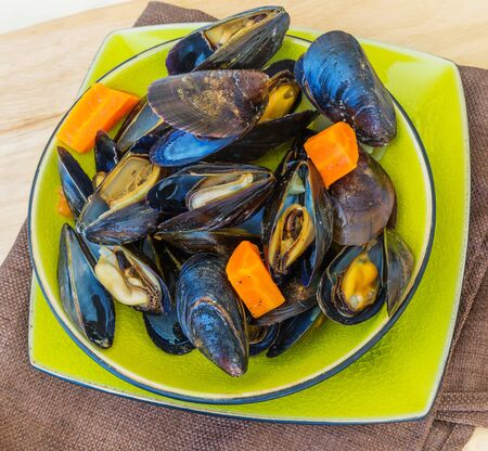 Cooked mussels with vegetables in a ceramic bowl.