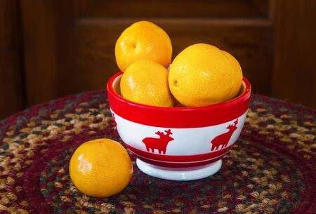 Holiday mandarin oranges in a Christmas themed bowl. Stock Photo