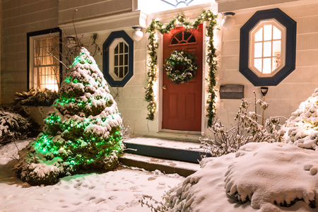home decorated: The front door of a snow covered family home decorated for Christmas. Stock Photo