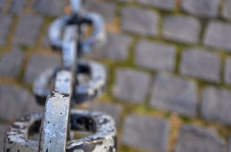 Rusty chain links over cobble stone side walk Stock Photo