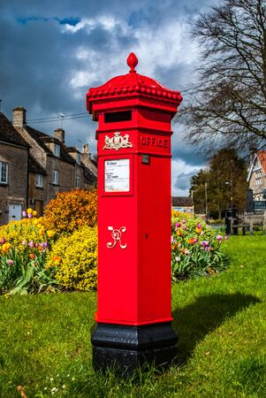 Tetbury, England, April 22 2012. Red post box in Tetbury Town. On grass with houses in background.