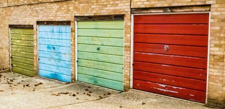 Row of four small garages with different coloured doors, Bracknell England