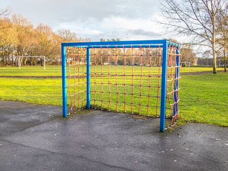 Small blue goal in a park with red netting. In a UK park in December on paved area.