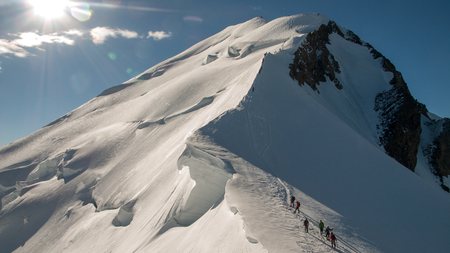 Alpinists climbing the highest mountain in Western Europe. Mont Blanc (French) or Monte Bianco (Italian), France and Italy.