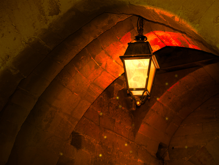 Fantasy scene, one street lamp hanging from the top of the arch in warm summer night.  Saint-Malo, France Stok Fotoğraf
