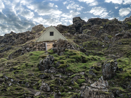 Small traditional rural historical vikings house in the countryside surrounded with green grass and moss with the blue sky and white clouds above. Iceland, Europe.