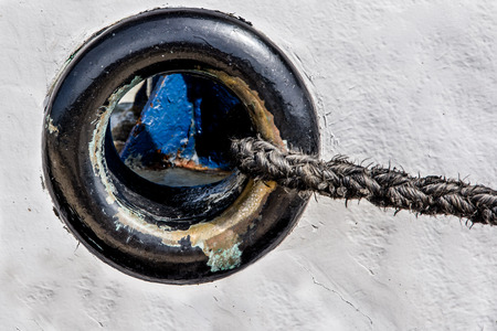 Close up view of black porthole on the iron white fisherman boat with black rope exiting on the right side.